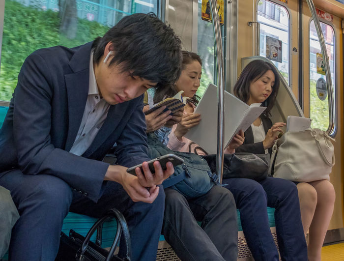 Rear view of friends using mobile phone while sitting in bus