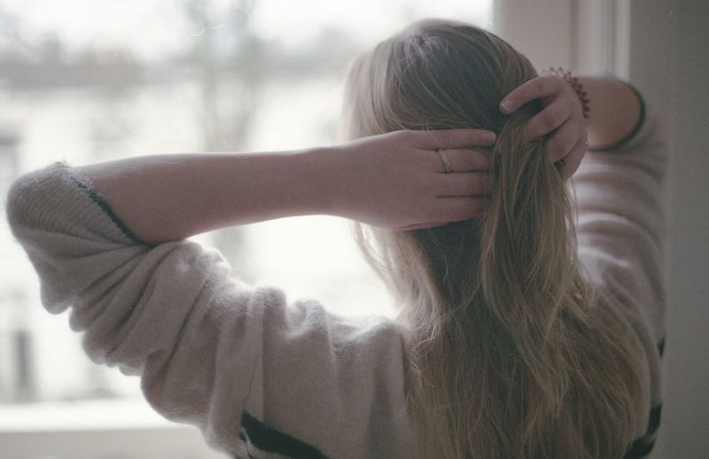 Rear view of woman with hand in hair standing at home
