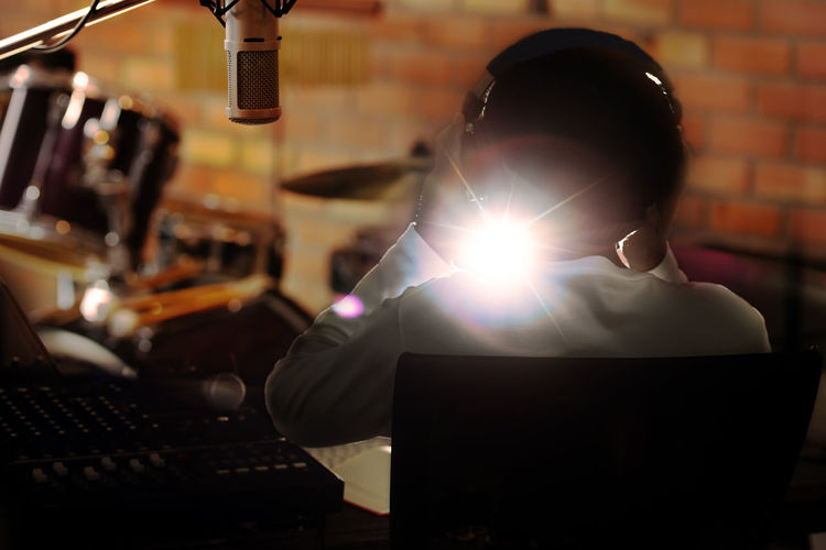 Light Beam Streaming Through Man Sitting In Recording Studio