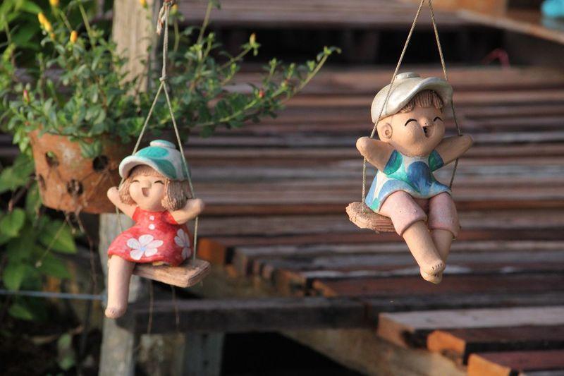 Close-up of child toys swinging at yard