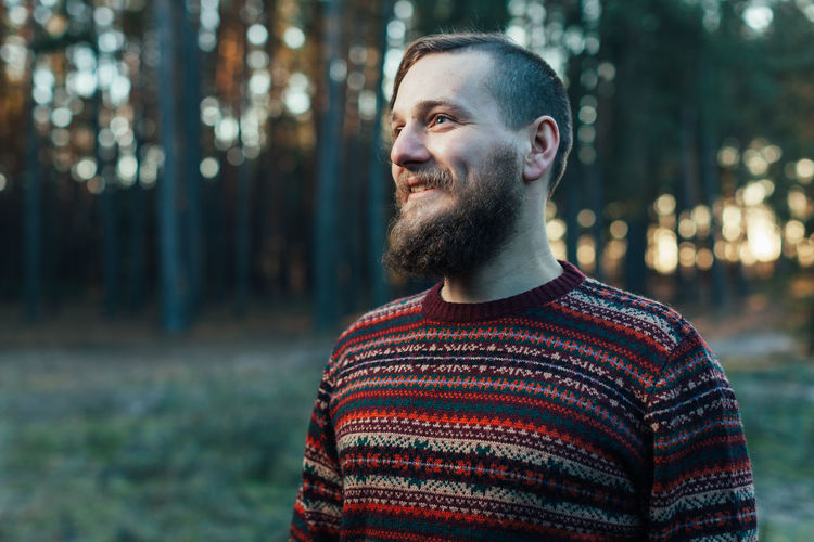 a young man with a beard walks in a pine forest. Portrait of a brutal bearded man Autumn forest tourism concept Adult Beard Casual Clothing Clothing Facial Hair Focus On Foreground Front View Happiness Looking Nature One Person Outdoors Portrait Real People Smiling Standing Sweater Waist Up Young Adult