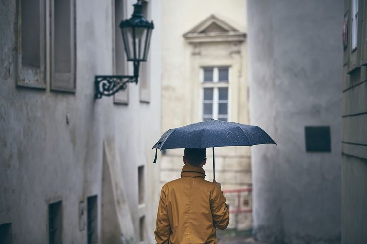 Rear view of man with umbrella walking against buildings during rainy season
