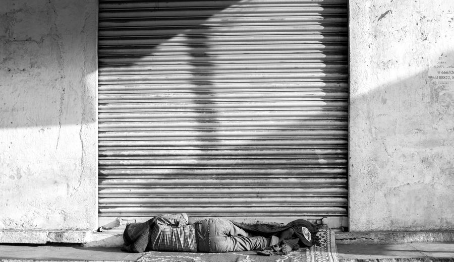 Man Sleeping On Road Against Closed Shutter