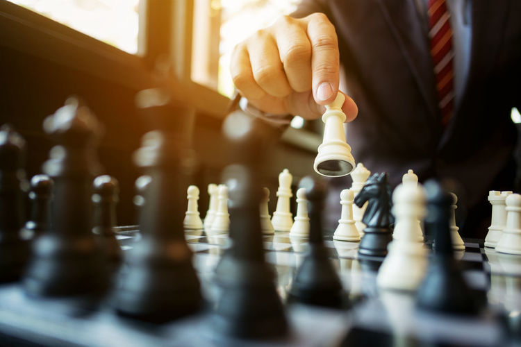 Midsection of businessman playing chess