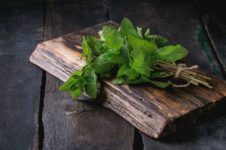 Bunch of fresh mint with thread on wooden chopping board over old wooden background. Dark rustic style Wood - Material Food And Drink Herb Mint Mint Leaf - Culinary Leaves Cutting Board Table Plant Part Leaf Food Dark Healthy Eating Green Color Plant Garnish