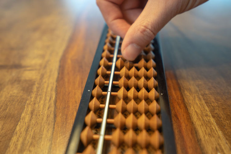Cropped image of person holding abacus on table