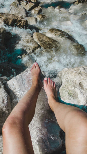 Low section of woman feet in water