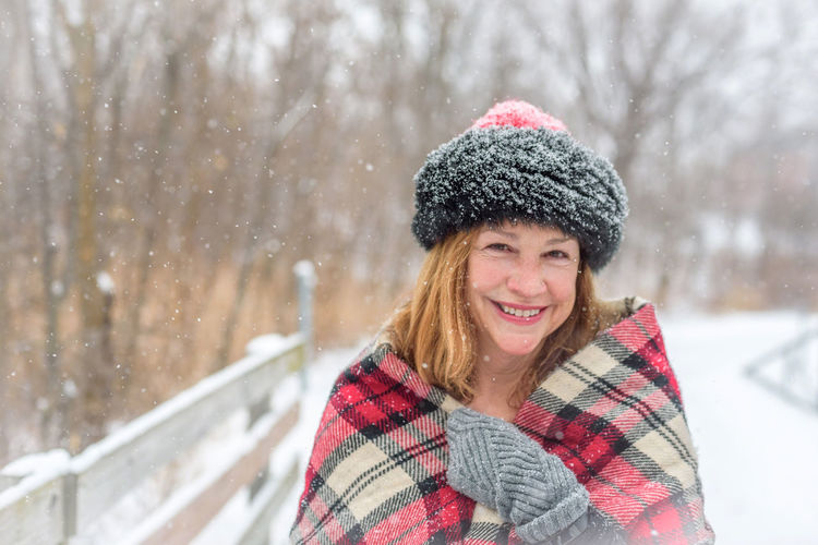 Close-up portrait of smiling woman during snowfall
