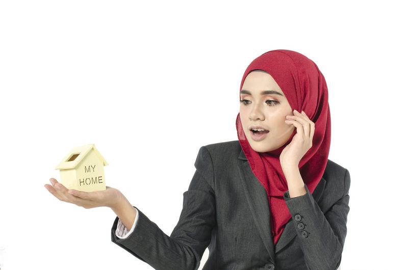 Surprised businesswoman holding house model against white background