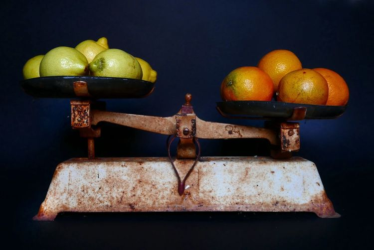 Close-up of fruits of old weight scale against colored background