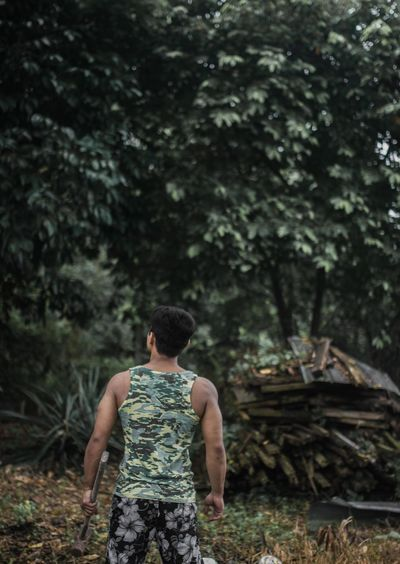 Rear view of young man standing in forest