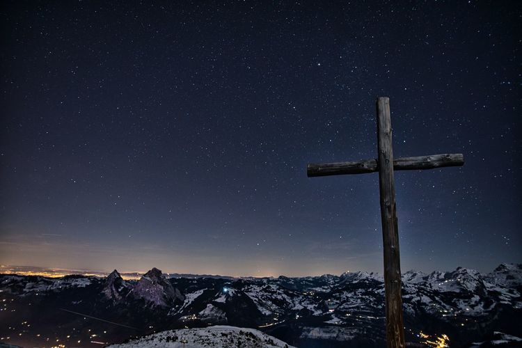 Low angle view of cross against sky at night