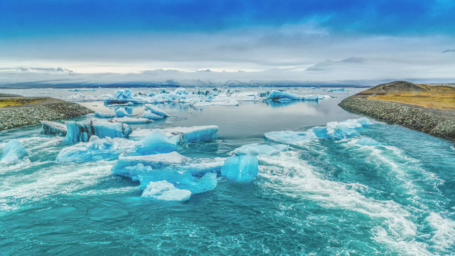 Blue blocks of ice floating in a glacier lake Jökulsárlón of southeast Iceland Beauty In Nature Blue Cold Temperature Day Frozen Glacier Ice Iceberg Iceberg - Ice Formation Idyllic Melting Nature No People Outdoors Scenics Sea Sky Tranquil Scene Tranquility Water Winter