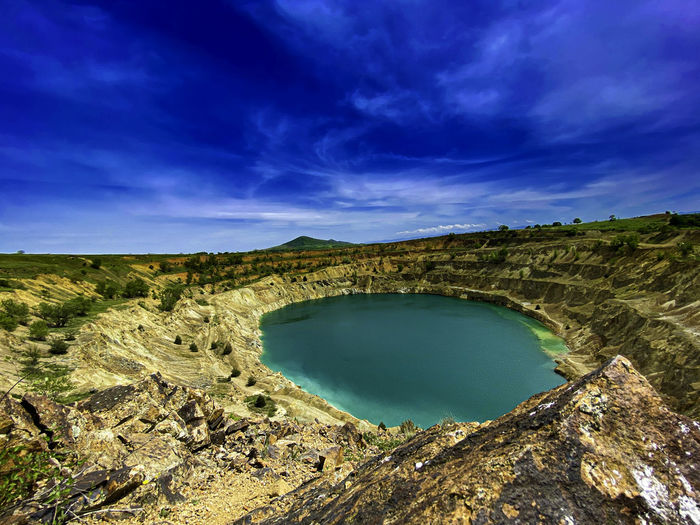 Scenic view of landscape against abandoned mine and blue sky