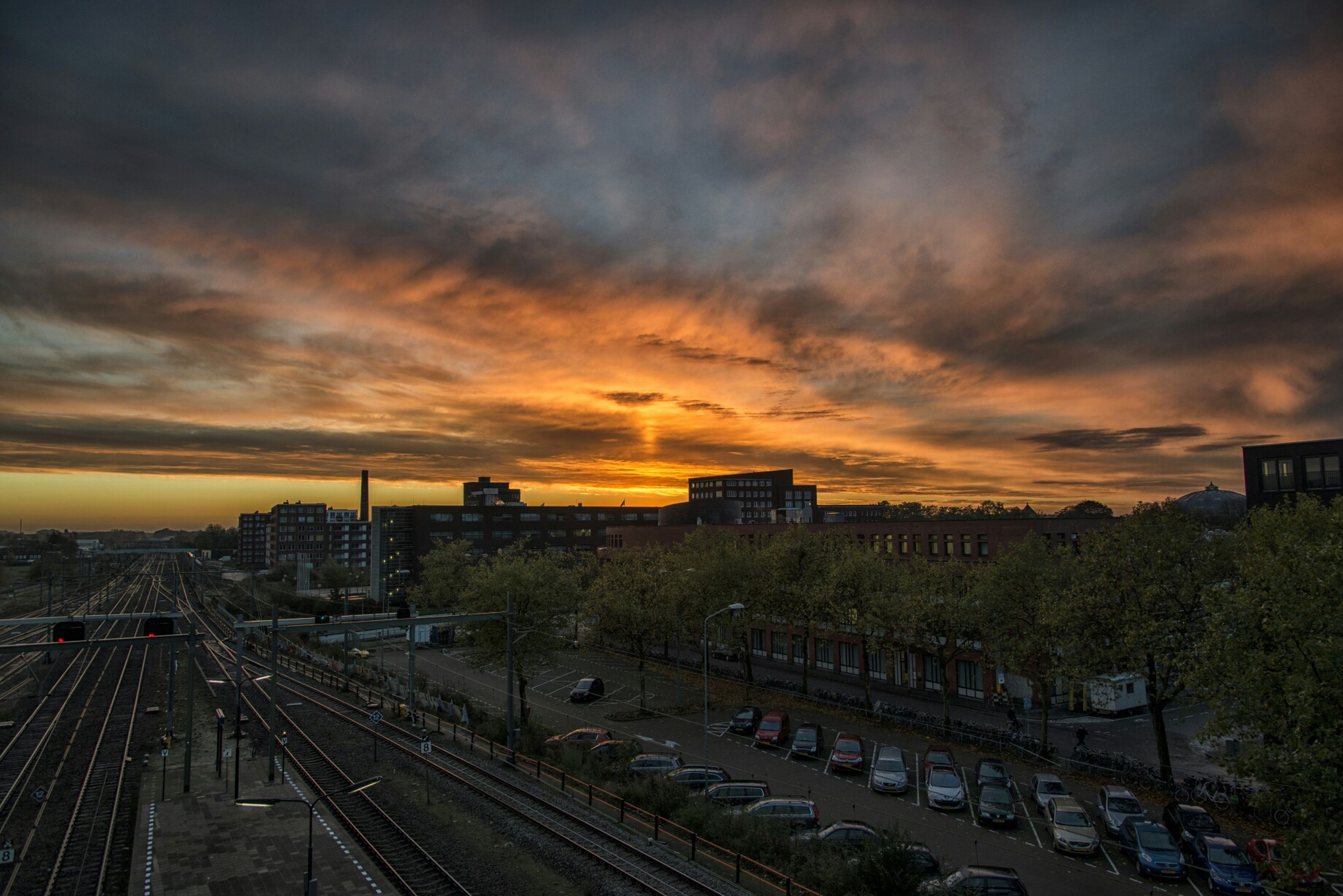 transportation, sunset, sky, cloud - sky, high angle view, architecture, land vehicle, railroad track, built structure, city, orange color, mode of transport, building exterior, car, cloudy, road, rail transportation, public transportation, the way forward, street