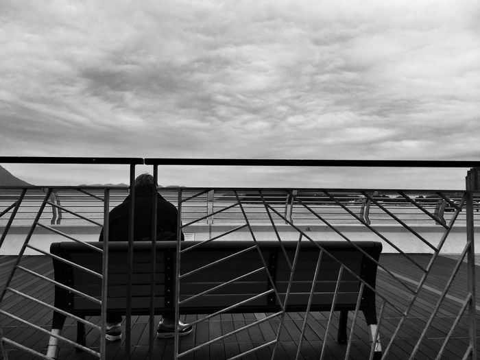 Rear View Of Man Sitting On Bench At Footbridge