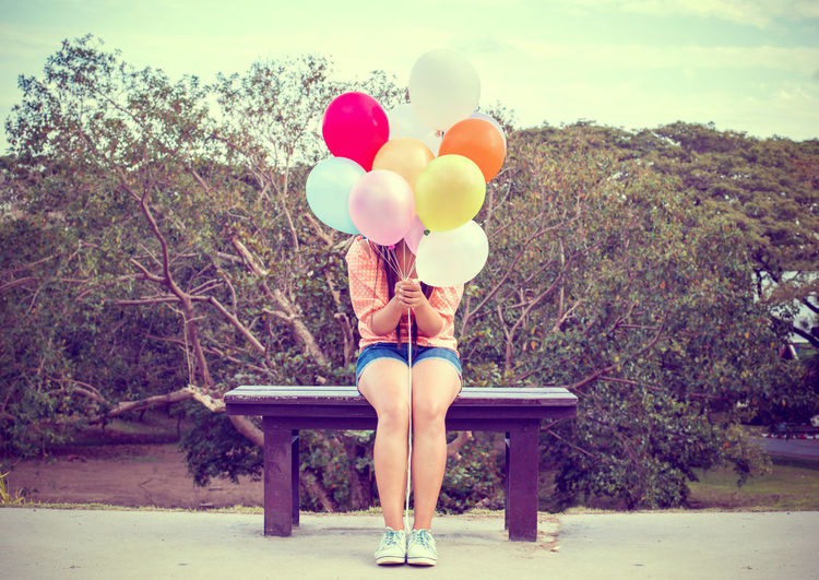 Vintage photo of Happy young woman holding colorful balloons and sitting on bench Girl Happiness Happy Balloons Festival Celebration Decoration Cheerful Woman Young Women Colorful Vintage Retro Styled Lifestyles Holiday