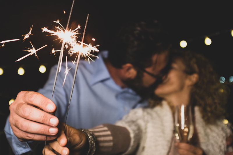 Couple kissing while holding sparklers at night