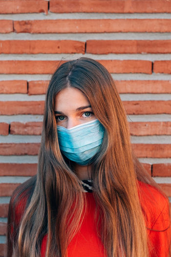 Close up portrait of young caucasian woman wearing face medical mask to prevent infection