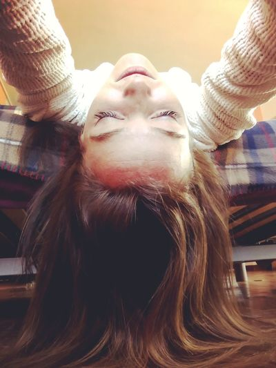 Low angle view of young woman lying on bed at home