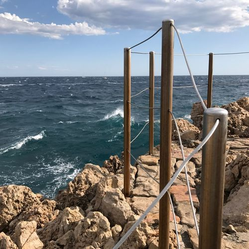 Fencing on rocks at sea against sky