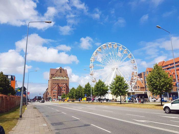 Ferris wheel by buildings against sky