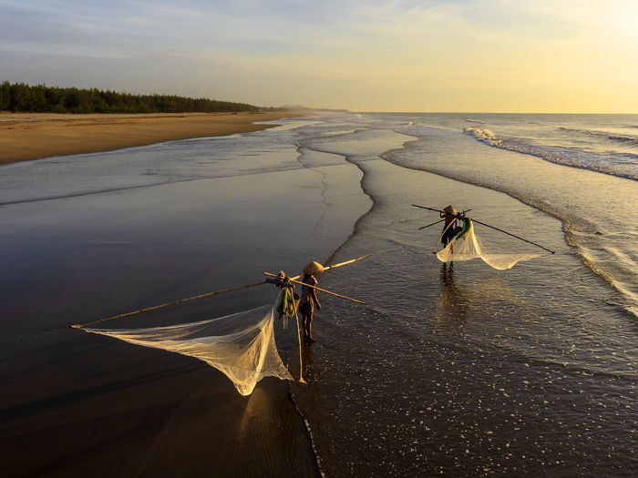 Fishermen With Fishing Nets Standing At Beach Against Sky During Sunset