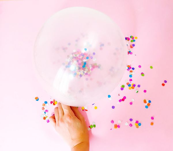 Close-up of hand holding balloon against pink background