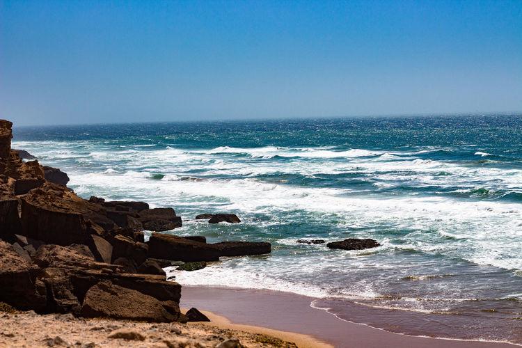 Coast Sea Water Land Sky Beach Horizon Wave Horizon Over Water Scenics - Nature Beauty In Nature Rock Rock - Object Sport Motion Surfing Aquatic Sport Solid Nature Clear Sky Outdoors Breaking Power In Nature