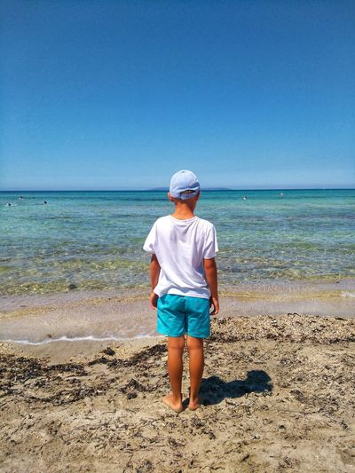Rear View Of Boy Standing At Beach Against Sky