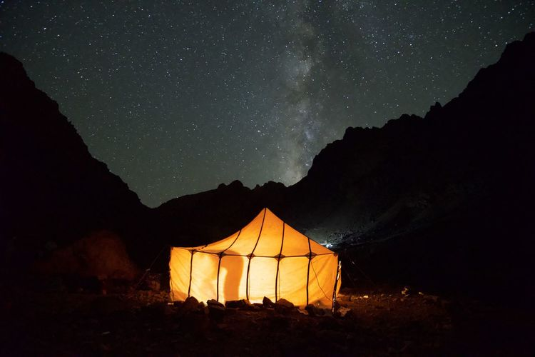 Illuminated tent on land against star field at night