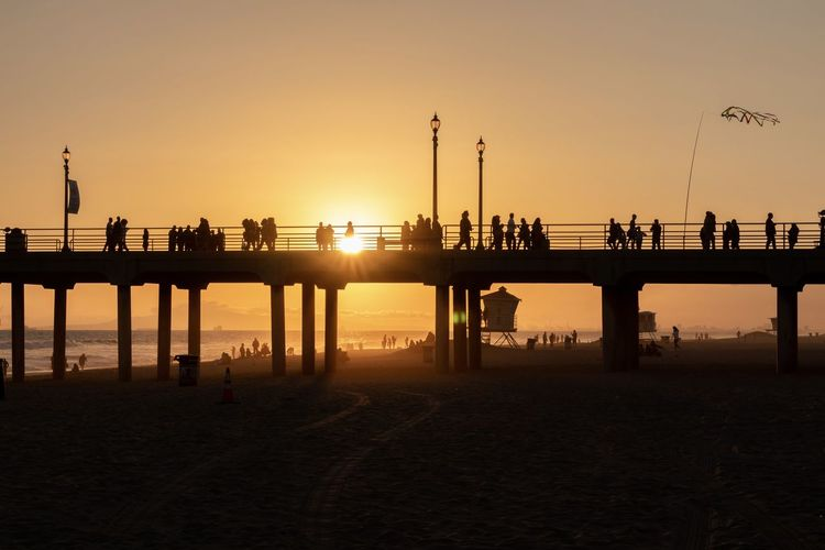 silhouettes of people and a pier at the beach Sky Sunset Built Structure Water Architecture Silhouette Bridge Nature Connection Orange Color Scenics - Nature Pier Sea Clear Sky Outdoors Sun Architectural Column Huntington Beach Pier Huntington Beach Beach Beach Life Dusk Orange Sunset Orange County Southern California