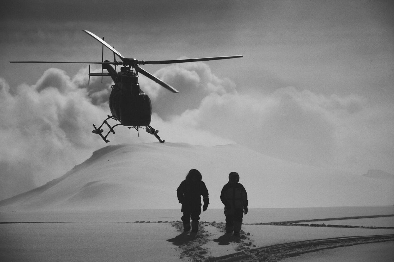 Helicopter over people standing on snowy field