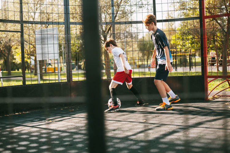 Two teenagers play freestyle soccer on a special playground. boys run after the ball. sport