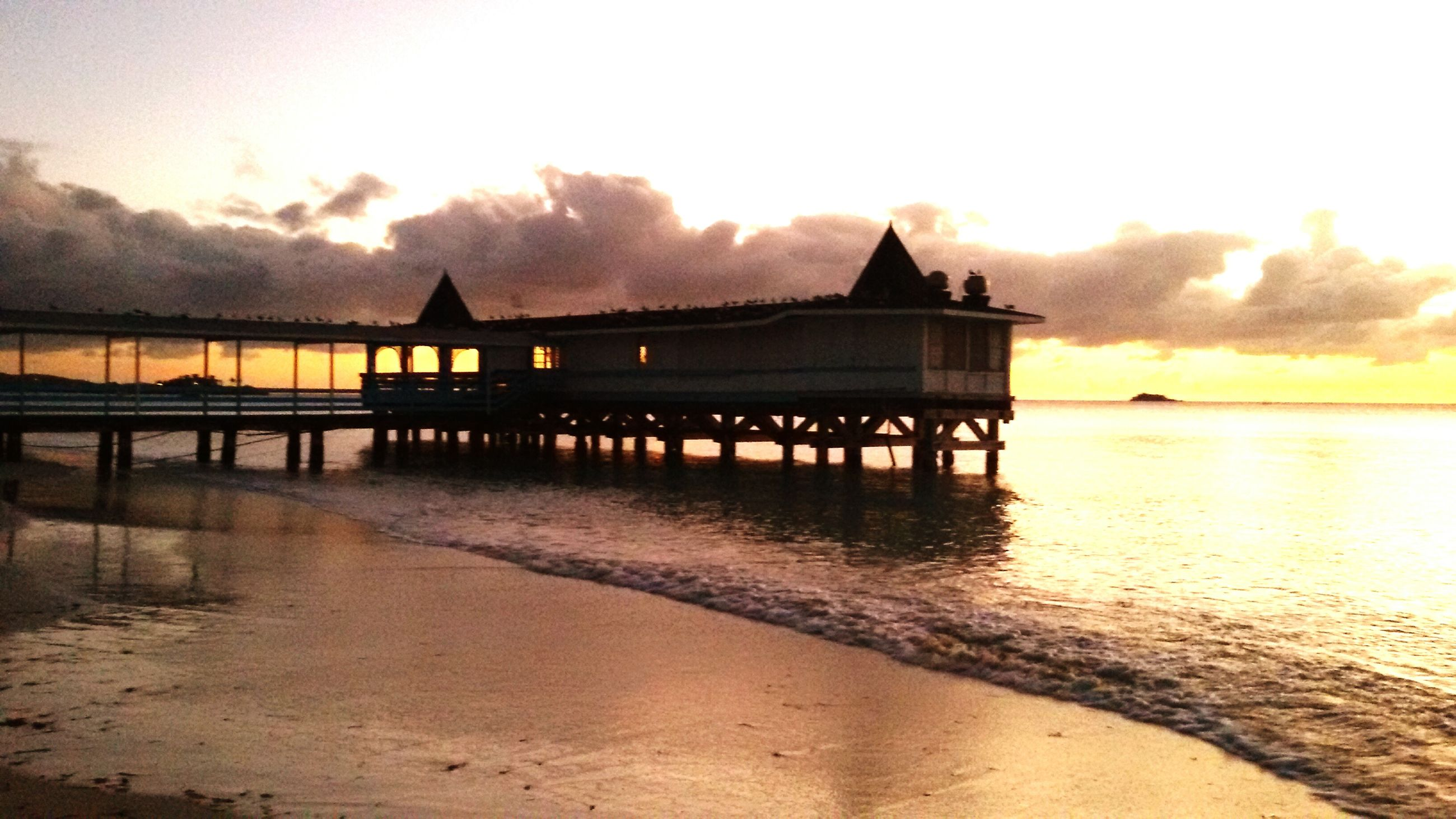 water, sunset, sea, pier, built structure, sky, beach, scenics, architecture, tranquility, tranquil scene, beauty in nature, reflection, silhouette, nature, shore, idyllic, cloud - sky, dusk, orange color
