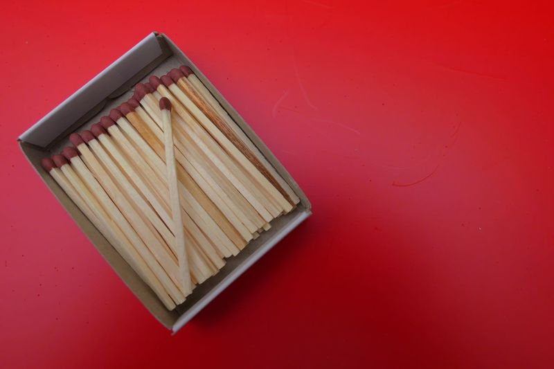 Close-Up Of Matchsticks In Box Over Red Background