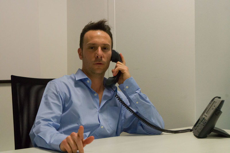Portrait Of Businessman Talking On Telephone While Sitting At Office
