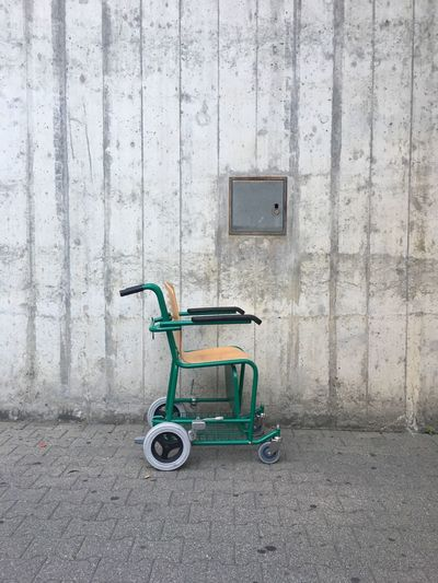 Empty wheelchair against wall