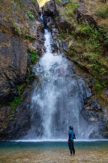 Man looking at waterfall