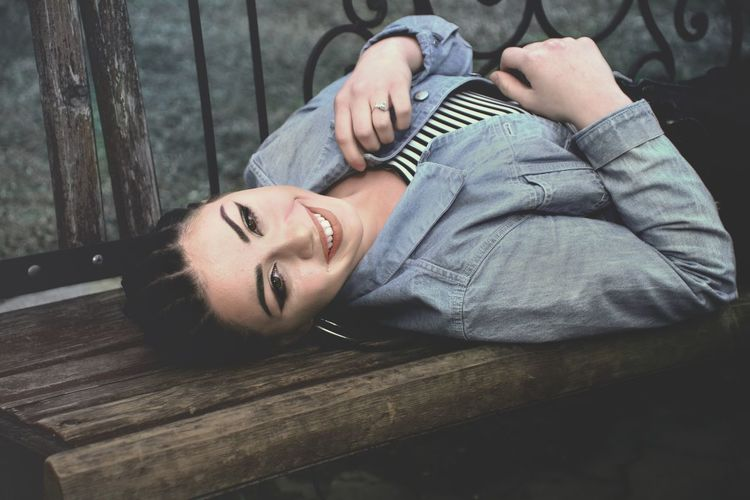 Portrait Of Smiling Young Woman Lying On Bench