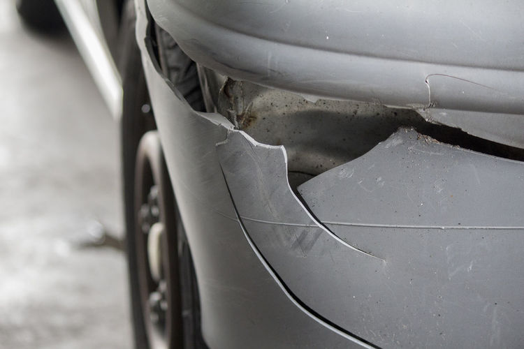 Close-up of a cracked rear signal lamp on a gray plastic bumper after the car accident, scratches obviously found on the bumper body. Car Close-up Cracked Day Land Vehicle Mode Of Transport No People Outdoors Stationary Tire Transportation Wheel