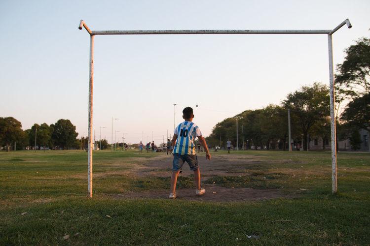Rear view of boy on field against sky