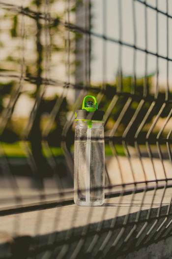 Close-up of bottle on retaining wall