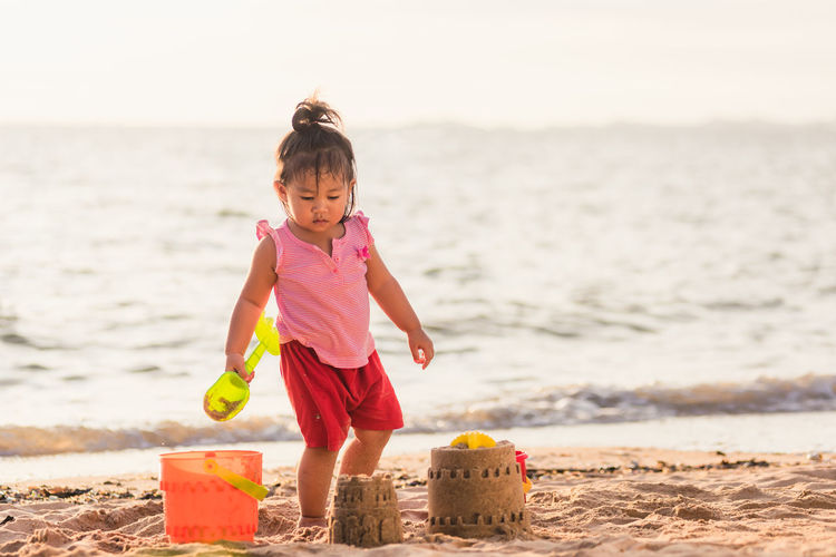 Full length of girl standing by sandcastle at beach