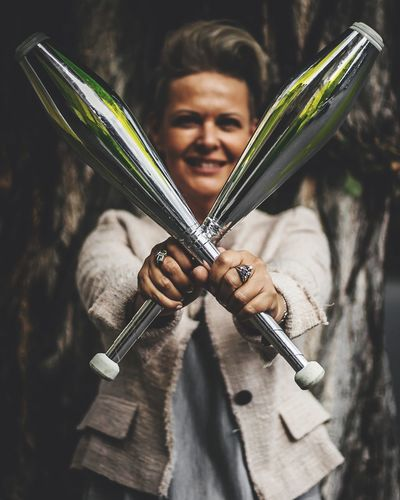 Portrait Of Smiling Woman Holding Juggling Clubs Outdoors