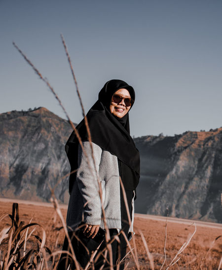 One Person Sky Leisure Activity Smiling Looking At Camera Real People Portrait Lifestyles Front View Clothing Standing Mountain Young Adult Nature Casual Clothing Land Warm Clothing Focus On Foreground Day Clear Sky