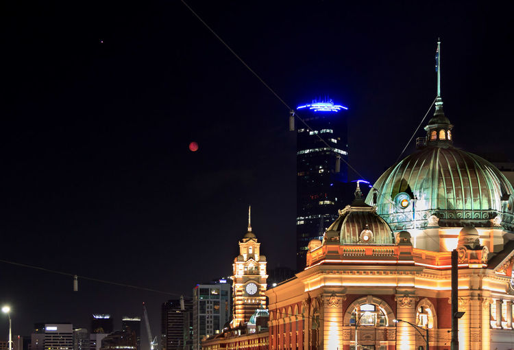 Illuminated flinders street station, buildings in city and super moon at night