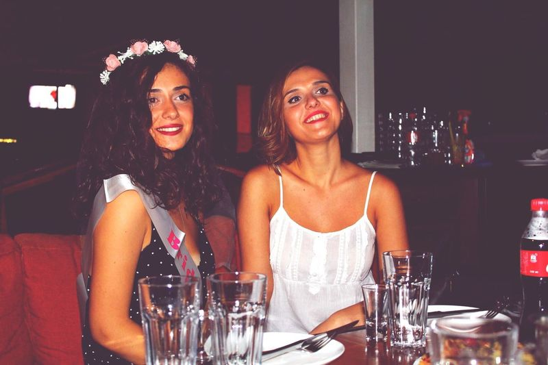 Female friends smiling while sitting at restaurant
