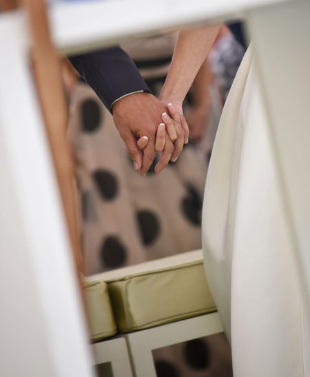 Cropped image of couple holding hands at home