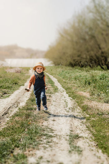 Full length of child running on a pathway in the country